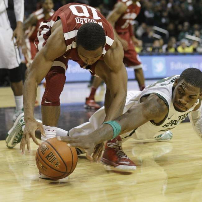 Michigan State's Branden Dawson (22) and Oklahoma's Jordan Woodard (10) fight for control of the ball during the second half of the championship game in the Coaches vs. Cancer NCAA college basketball game Sunday, Nov. 24, 2013, in New York. Michigan State won 87-76