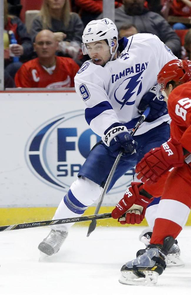 Tampa Bay Lightning's Tyler Johnson (9) takes a shot on goal against Detroit Red Wings' Danny DeKeyser (65) during the first period of an NHL hockey game Sunday, March 30, 2014, in Detroit. The Red Wings defeated the Lightning 3-2