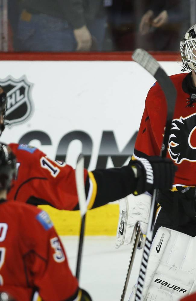 Calgary Flames goalie Karri Ramo, centre, from Finland, celebrates with teammates following their overtime win in NHL hockey action against the San Jose Sharks in Calgary, Monday, March 24, 2014. The Flames beat the Sharks 2-1 in a shootout