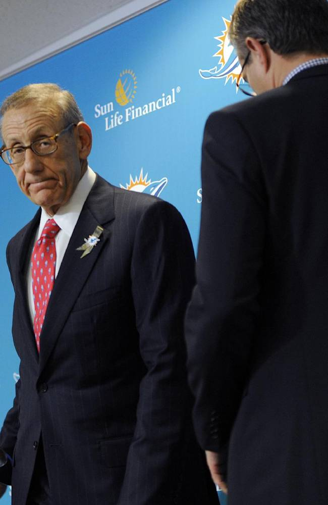 Miami Dolphins owner Stephen Ross, left, and CEO Tom Garfinkel cross paths as they address the media before an NFL football game against the Tampa Bay Buccaneers Monday, Nov. 11, 2013, in Tampa, Fla