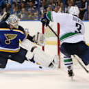 St. Louis Blues goaltender Jake Allen defends Vancouver Canucks defenseman Kevin Bieksa during the second period of an NHL hockey game Thursday, Oct. 23, 2014, in St. Louis. The Canucks won 4-1 The Associated Press