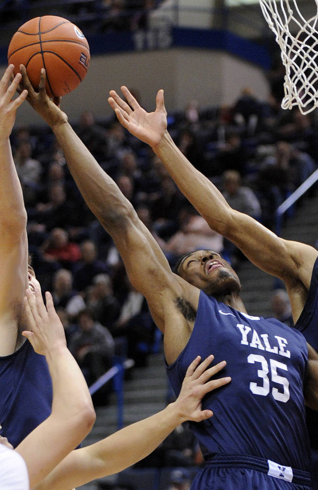 Yale's Nick Victor, left, Brandon Sherrod, second from right,  and Javier Duren, right, fight for a rebound as Connecticut's Omar Calhoun watches during the first half of an NCAA college basketball game, in  Hartford, Conn., on Monday, Nov. 11, 2013