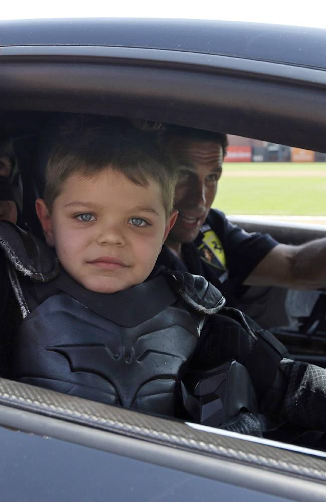 Miles Scott, dressed as Batkid, gestures as he sits in the Batmobile after throwing the ceremonial first pitch before an opening day baseball game between the San Francisco Giants and the Arizona Diamondbacks in San Francisco, Tuesday, April 8, 2014. On Nov. 15, 2013, Scott, a Northern California boy with leukemia, fought villains and rescued a damsel in distress as a caped crusader through The Greater Bay Area Make-A-Wish Foundation