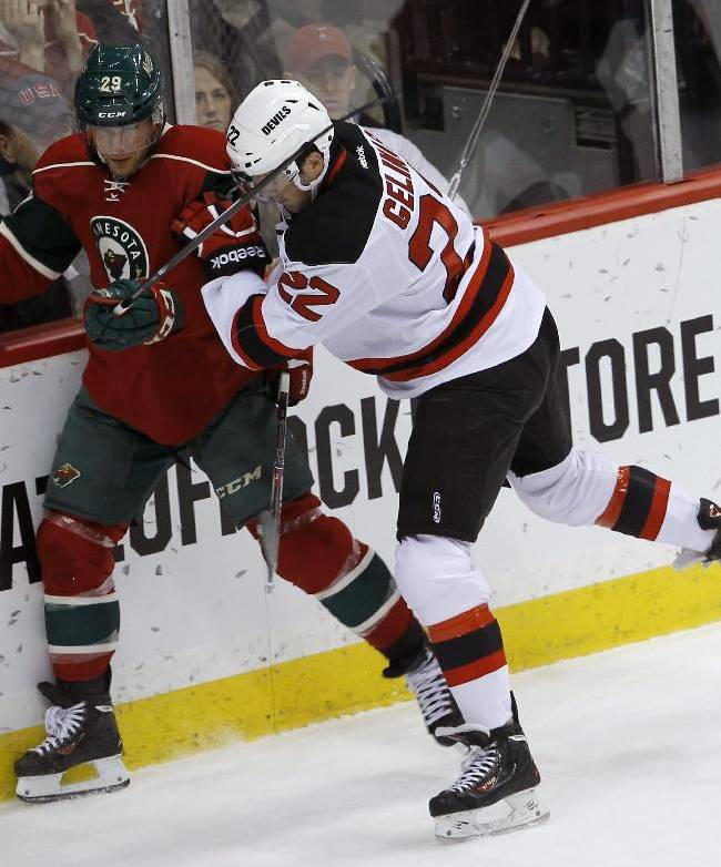 New Jersey Devils defenseman Eric Gelinas (22) checks Minnesota Wild right wing Jason Pominville (29) off the puck during the first period of an NHL hockey game in St. Paul, Minn., Sunday, Nov. 3, 2013
