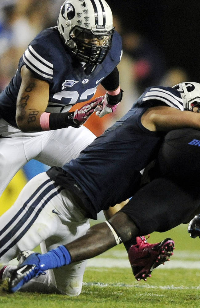 Boise State Broncos running back Jay Ajayi (27) is tackled by Brigham Young Cougars linebacker Alani Fua (5) during a game at Lavell Edwards Stadium on Friday,  Oct. 25, 2013, in Provo, Utah