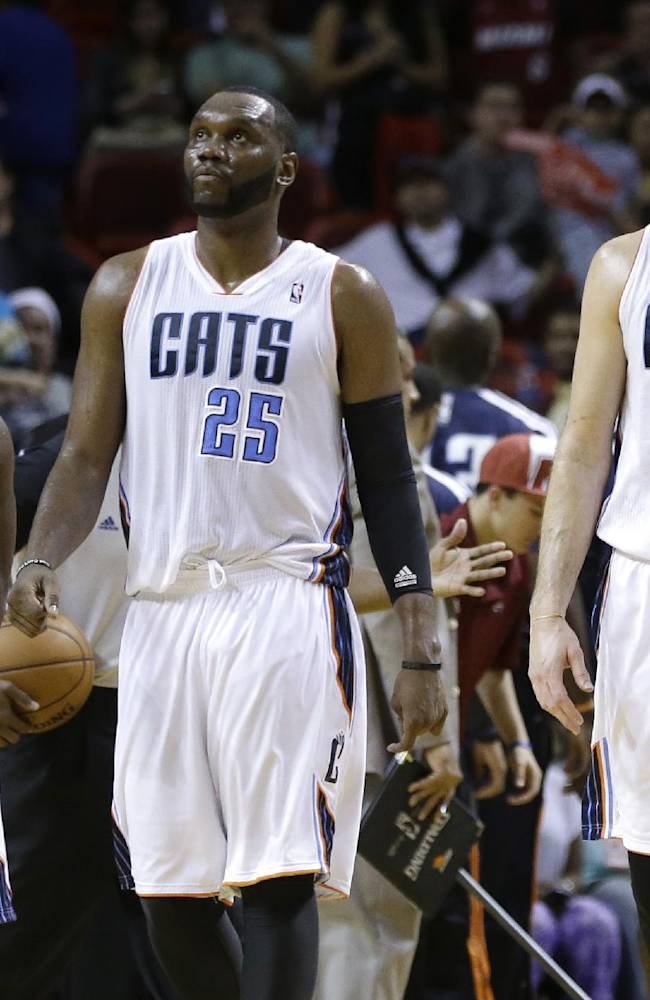 Charlotte Bobcats' Kemba Walker (15), Al Jefferson (25) and Josh McRoberts (11) walk onto the court late in the fourth quarter of an NBA basketball game against the Miami Heat, Sunday, Dec. 1, 2013, in Miami. The Heat defeated the Bobcats 99-98