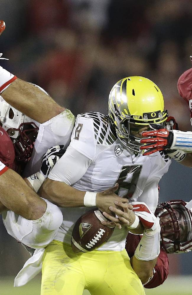 Oregon quarterback Marcus Mariota (8) fumbles as he is tackled by Stanford defensive tackle David Parry, left, linebacker A.J. Tarpley, rear, and linebacker Jarek Lancaster, right, during the third quarter of an NCAA college football game in Stanford, Calif., Thursday, Nov. 7, 2013. Stanford recovered the fumble