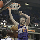 Phoenix Suns center Miles Plumlee, center, stuffs over Sacramento Kings' Greivis Vasquez, of Venezuela and Ben McLemore, right, during the first quarter of an NBA basketball game in Sacramento, Calif., Tuesday, Nov. 19, 2013 The Associated Press