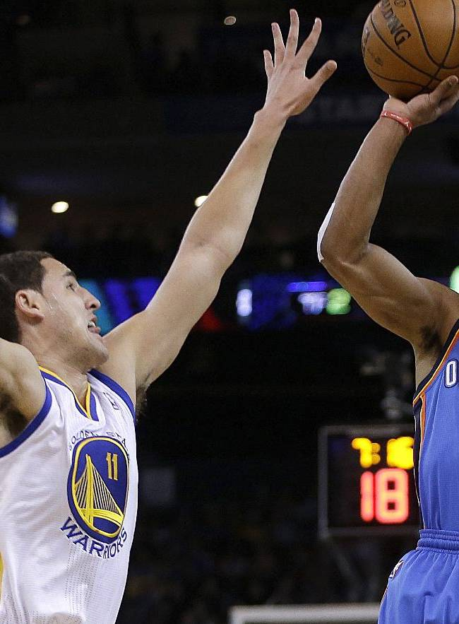Oklahoma City Thunder's Russell Westbrook, right, shoots over Golden State Warriors' Klay Thompson (11) during the first half of an NBA basketball game Thursday, Nov. 14, 2013, in Oakland, Calif