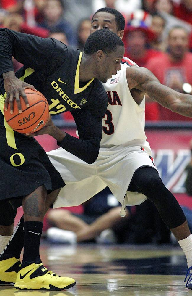 Oregon's Jason Calliste (12) looks to pass against the defense of Arizona's Rondae Hollis-Jefferson, in back, in the second half of an NCAA college baskettball game on Thursday, Feb. 6, 2014 in Tucson, Ariz. Arizona won 67 - 65