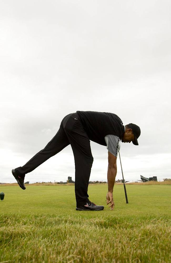 Tiger Woods of the US picks up his ball after playing a shot off the 17th tee during a practice round at Royal Liverpool Golf Club prior to the start of the British Open Golf Championship, in Hoylake, England, Saturday, July 12, 2014. The 2014 Open Championship starts on Thursday, July 17