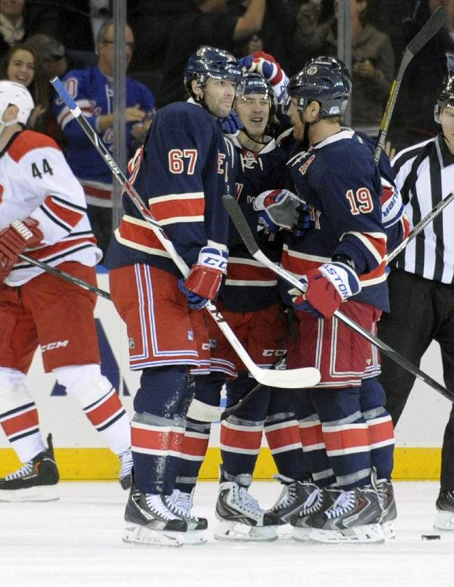 New York Rangers' Benoit Pouliot (67) and Brad Richards (19) celebrate with Carl Hagelin after Hagelin scored, as Carolina Hurricanes' Jay Harrison, rear, skates away during the first period of an NHL hockey game Saturday, Nov. 2, 2013, at Madison Square Garden in New York