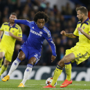 Chelsea's Willian, centre, vies for the ball with Maribor's Zeljko Filipovic during the Champions League Group G soccer match between Chelsea and NK Maribor at Stamford Bridge stadium in London Tuesday, Oct. 21, 2014