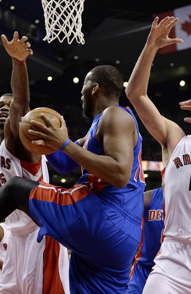 Toronto Raptors forward Amir Johnson, left, and center Jonas Valanciunas, right, try to block Detroit Pistons forward Greg Monroe during first-half NBA basketball game action in Toronto, Wednesday, Jan. 8, 2014