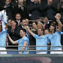Manchester City's Vincent Kompany, left, lifts the winners trophy after his team's 3-1 win against Sunderland during the League Cup Final at Wembley Stadium, London, England, Sunday, March 2, 2014