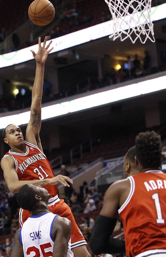 Milwaukee Bucks' John Henson (31) shots the ball over Philadelphia 76ers' Henry Sims during the second half of an NBA basketball game, Monday, Feb. 24, 2014, in Philadelphia. The Bucks won 130-110