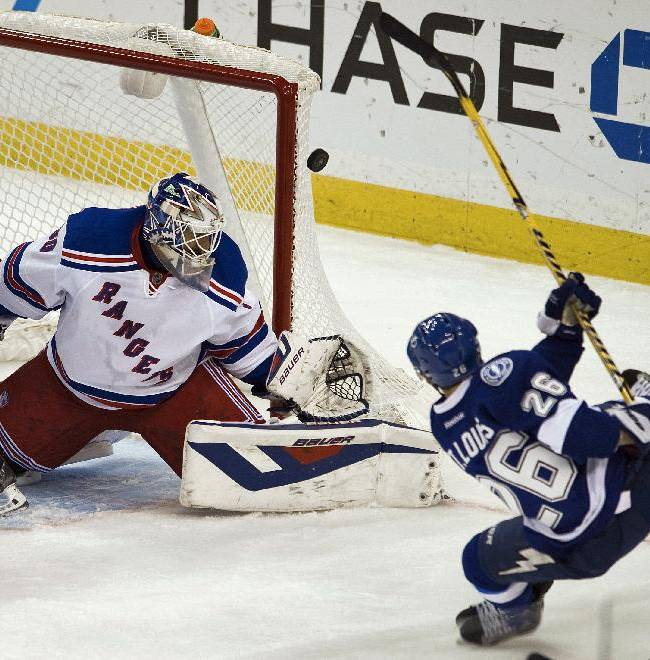 New York Rangers goalie Henrik Lundqvist (30) defends the net as Tampa Bay Lightning's Martin St. Louis (26) gets off a shot during the first period of an NHL hockey game, Sunday, Dec. 29, 2013, in Tampa, Fla