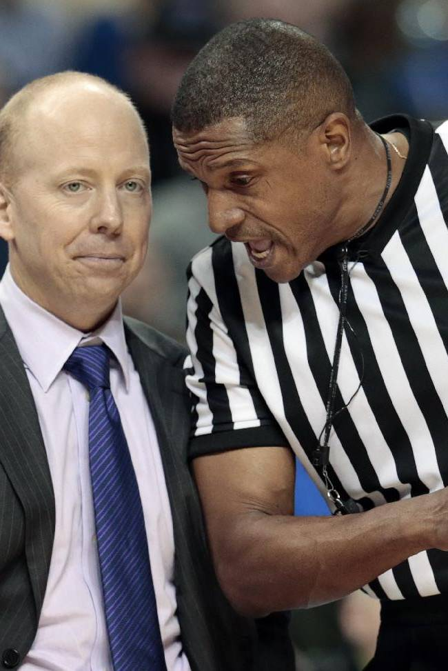 Official Ted Valentine, right, explains a call to Cincinnati head coach Mick Cronin in the second half of an NCAA college basketball game against Memphis Saturday, Jan. 4, 2014, in Memphis, Tenn. Cincinnati won 69-53