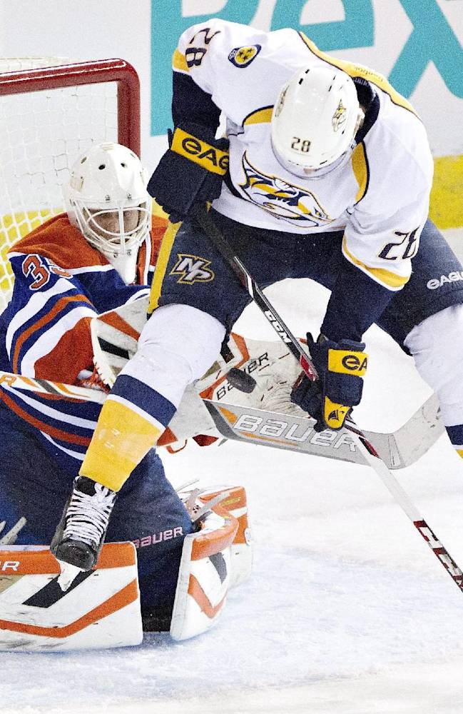 Nashville Predators' Paul Gaustad (28) tries to screen Edmonton Oilers goalie Viktor Fasth (35) as he makes the save during third period NHL hockey action in Edmonton, Alberta, on Tuesday March 18, 2014