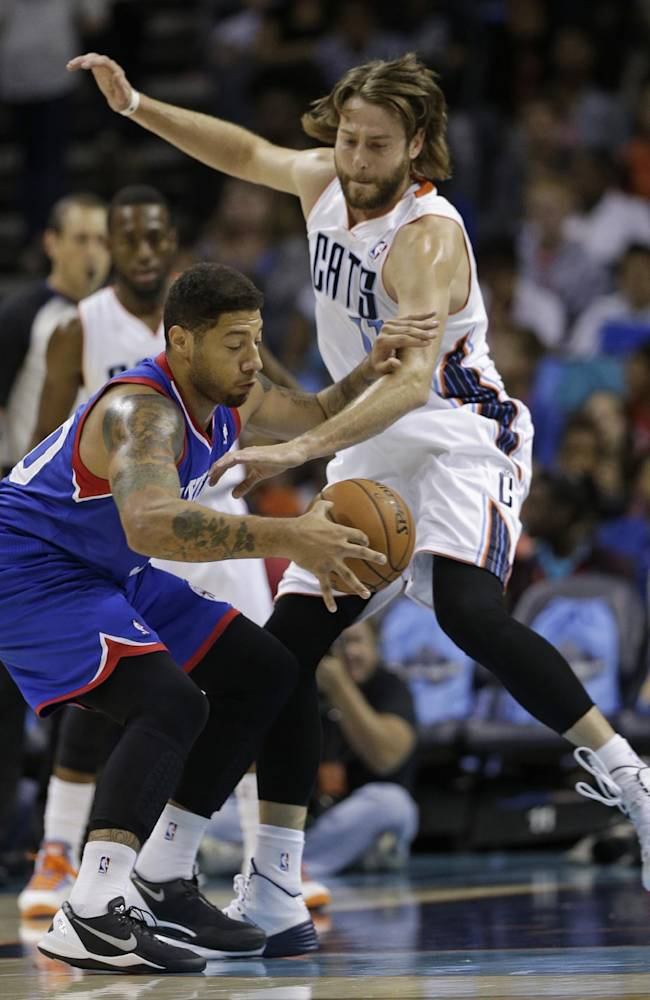 Charlotte Bobcats' Josh McRoberts, right, knocks the ball from Philadelphia 76ers' Royce White, left, during the first half of a preseason NBA basketball game in Charlotte, N.C., Thursday, Oct. 17, 2013