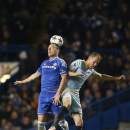 Chelsea's John Terry heads the ball in front of Bucharest's Pantelis Kapetanos during the Champions League Group E soccer match between Chelsea and Steaua Bucharest at Stamford Bridge Stadium in London Wednesday, Dec. 11, 2013
