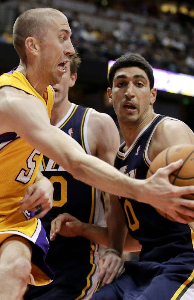 Los Angeles Lakers guard Steve Blake, left, passes around Utah Jazz center Enes Kanter during the first half of a preseason NBA basketball game in Anaheim, Calif., Friday, Oct. 25, 2013