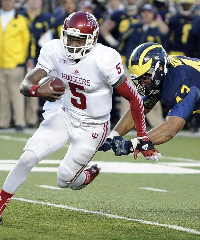 In this Oct. 19, 2013, file photo, Indiana quarterback Tre Roberson (5) runs past Michigan defensive end Chris Wormley and into the end zone for a fourth quarter touchdown during their NCAA football game at Michigan Stadium in Ann Arbor. Roberson is leaving Indiana and will transfer to another school
