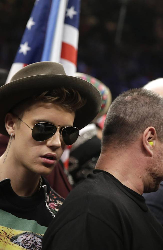 Justin Bieber, left, enters the arena before the start of the WBC-WBA welterweight title boxing fight between Floyd Mayweather Jr. and Marcos Maidana Saturday, May 3, 2014, in Las Vegas