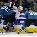 Colorado Avalanche's Jamie McGinn, center, is pressed against the boards by San Jose Sharks' Joe Thornton (19) and Dan Boyle, right, during the second period of an NHL hockey game on Friday, April 11, 2014, in San Jose, Calif The Associated Press