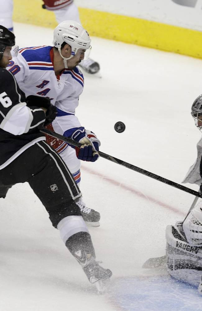 Los Angeles Kings goalie Jonathan Quick, right, blocks a shot by New York Rangers left wing Chris Kreider, middle, with the help of defenseman Jake Muzzin during the first period of Game 2 in the NHL hockey Stanley Cup Finals in Los Angeles, Saturday, June 7, 2014