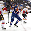 Calgary Flames' Paul Byron (32) checks Edmonton Oilers' Ryan Nugent-Hopkins (93) as Mikael Backlund (11) looks for the puck during the first period of an NHL hockey game Saturday, March 22, 2014, in Edmonton, Alberta The Associated Press