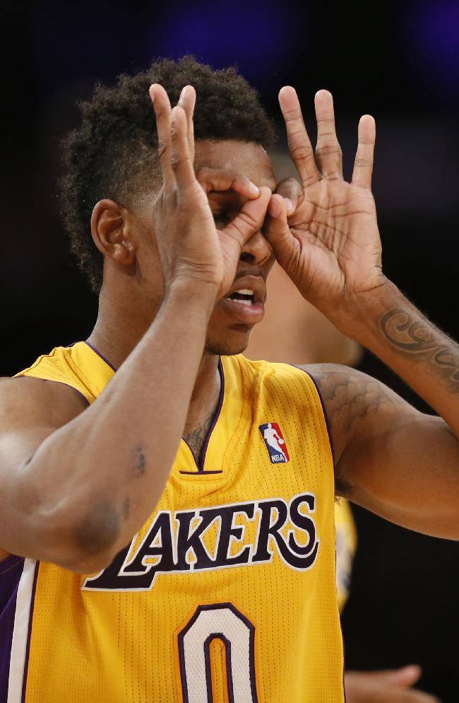 Los Angeles Lakers forward Nick Young puts his fingers around his eyes as he celebrates a three-pointer against the Portland Trail Blazers during the second half of an NBA basketball game in Los Angeles, Tuesday, April 1, 2014