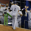 Colorado Rockies' Troy Tulowitzki (2) is greeted at the dugout by hitting coach Blake Doyle (25) and Michael Cuddyer, left, after scoring on a single by Nolan Arenado during the fifth inning of a baseball game against the Miami Marlins, Thursday, April 3,