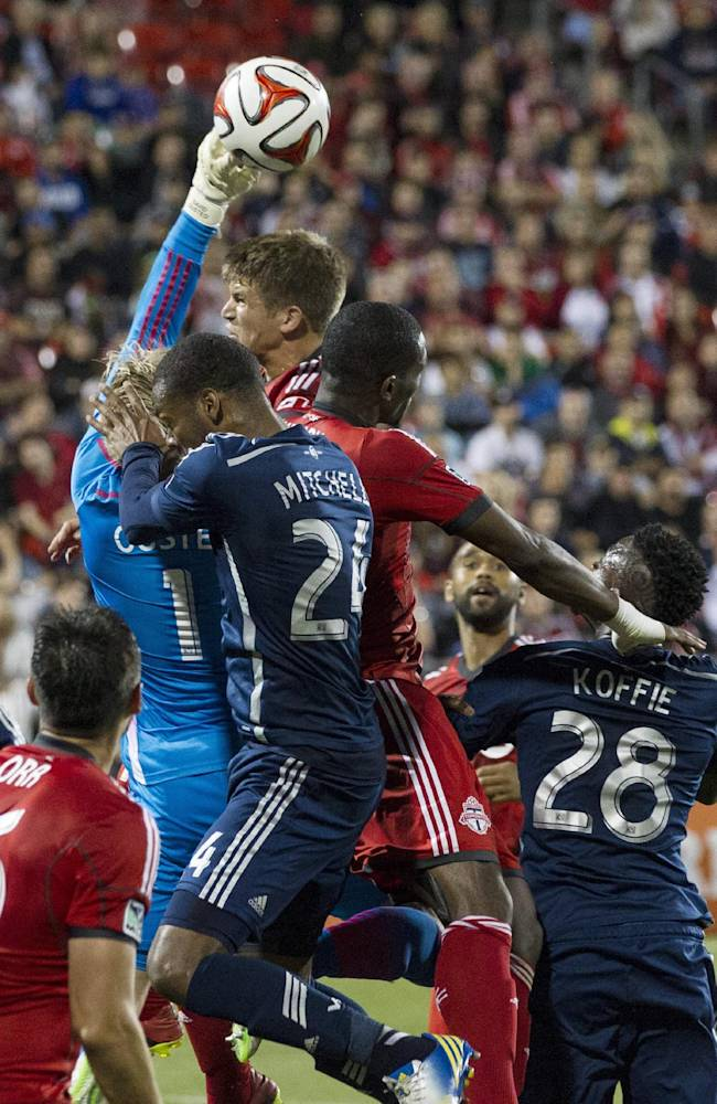 Vancouver Whitecaps goalkeeper David Ousted, center left, clears under pressure from Toronto FC 's Nick Hagglund, center, and Doniel Henry, right, as Vancouver's Carlyle Mitchell covers during the first half of a soccer game, Wednesday, July 16, 2014 in Toronto