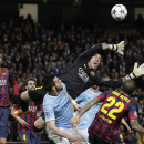 Barcelona goalkeeper Victor Valdes jumps for the ball next to Manchester City's Scott Sinclair and Barcelona's Daniel Alves, right, during their Champions League first knock out round soccer match at the Etihad Stadium, Manchester, England, Tuesday Feb. 1