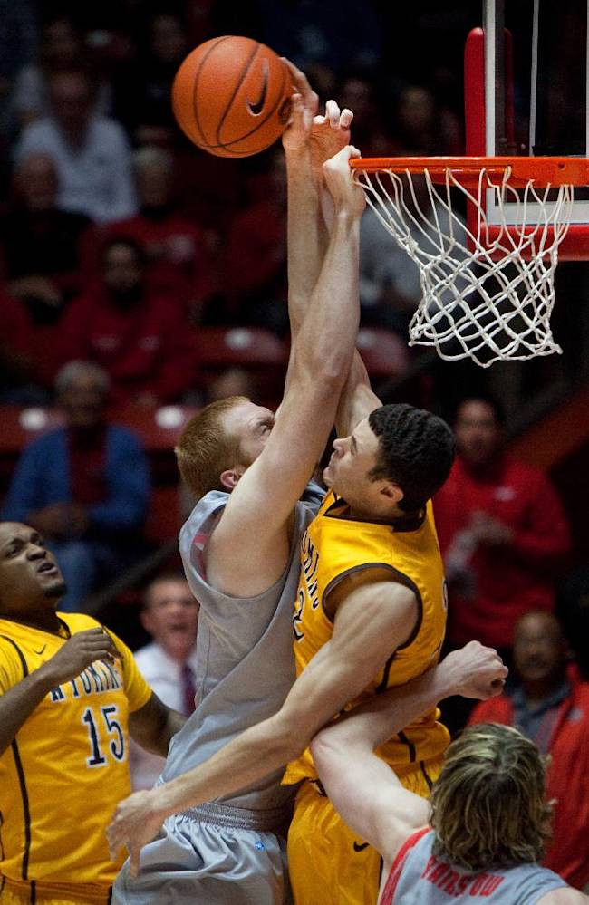 Wyoming's Larry Nance Jr., right, blocks a dunk attempt by New Mexico's Alex Kirk in the second half of an NCAA college basketball game Wednesday, Feb. 5, 2014 in Albuquerque, N.M. New Mexico won in overtime 66-61