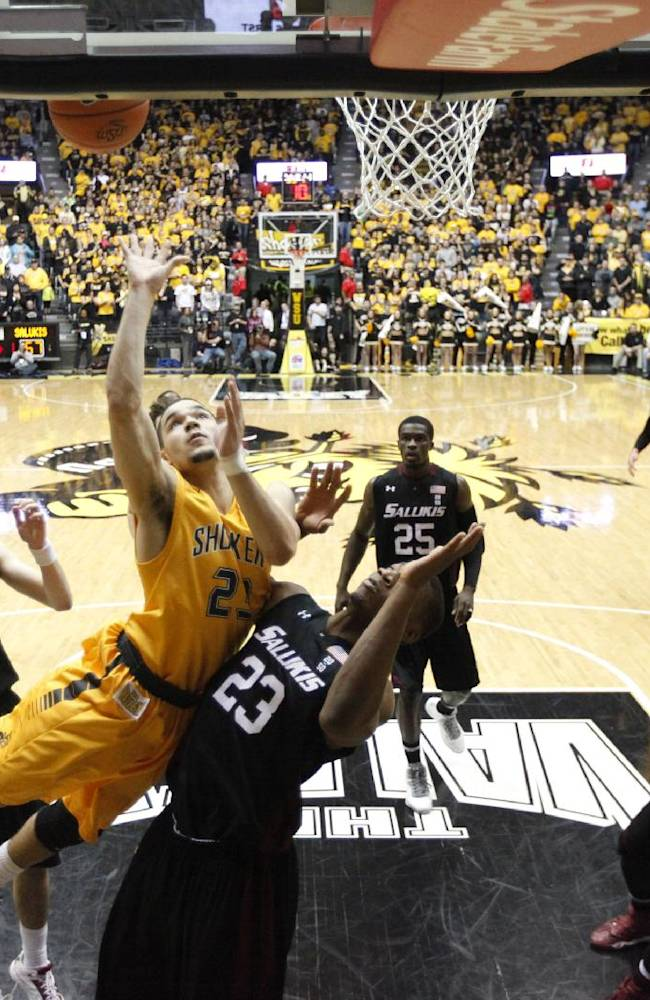 Wichita States Fred VanVleet shoots the ball while falling to the floor against Southern Illinois' Bola Olaniyan (23) during the second half of an NCAA college basketball game Tuesday, Feb. 11, 2014, in Wichita, Kan