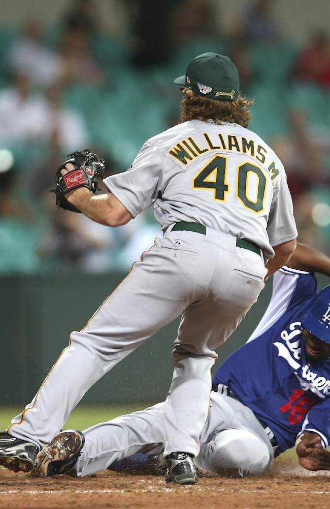 Los Angeles' Chone Figgins, right, slides in safe at home as Team Australia's Matt Williams covers after a passed ball during their exhibition baseball game at the Sydney Cricket Ground in Sydney, Thursday, March 20, 2014. The Arizona Diamondbacks and the Dodgers open the Major League Baseball regular season with games on Saturday and Sunday