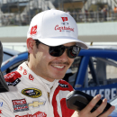 Kyle Larson smiles as he sits on the wall after the NASCAR Nationwide series auto race qualification in Homestead, Fla., Saturday, Nov. 15, 2014. (AP Photo/Terry Renna)