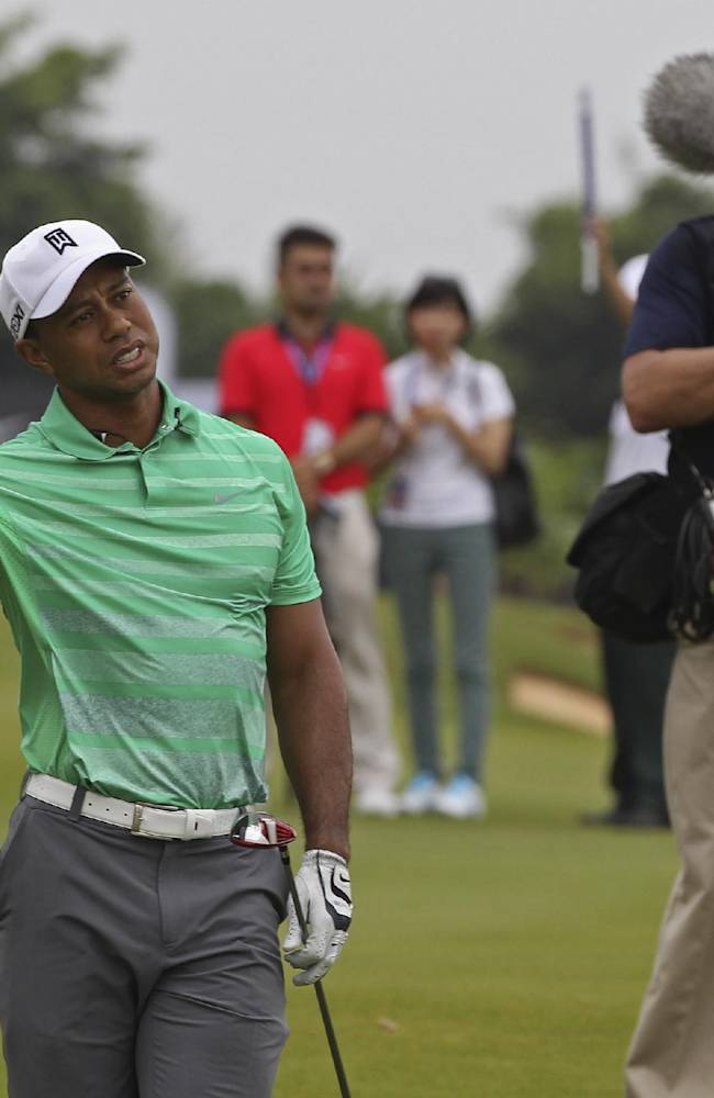 Tiger Woods of the United States reacts during an exhibition golf match against Rory Mcllory of Northern Ireland in Haikou, in southern China's island province Hainan, Monday, Oct. 28, 2013