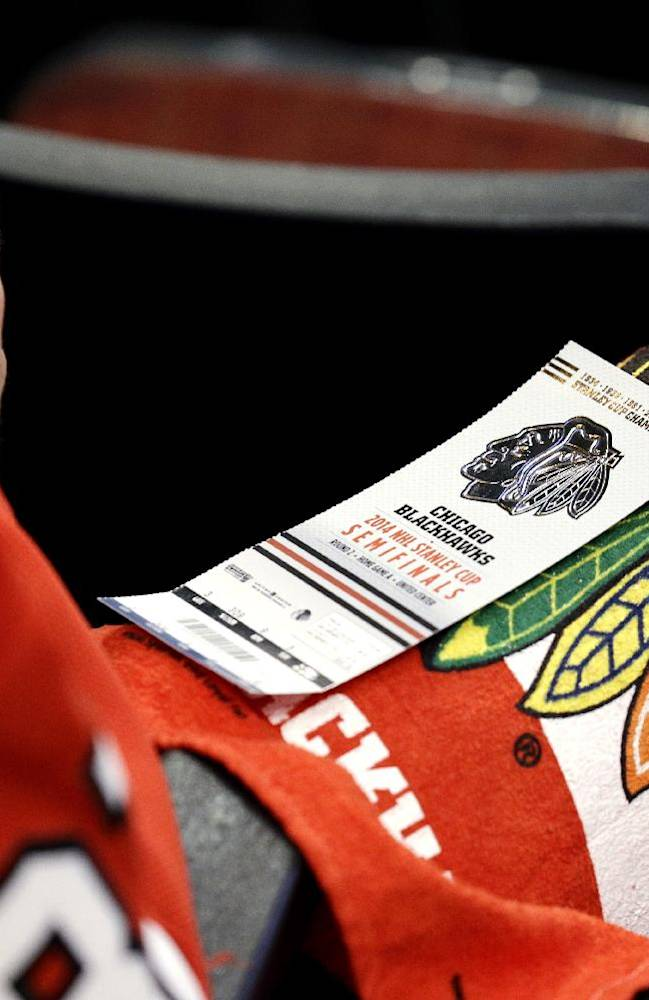 A fan has a game ticket on his lap before Game 1 of an NHL hockey second-round playoff series between the Minnesota Wild and the Chicago Blackhawks in Chicago, Friday, May 2, 2014
