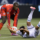 D.C. United goalkeeper Bill Hamid, left, picks up the ball as Vancouver Whitecaps' Mehdi Ballouchy, of Morocco, tumbles to the ground on a scoring chance during the second half of an MLS soccer game, Saturday, Sept. 6, 2014 in Vancouver, British Columbia