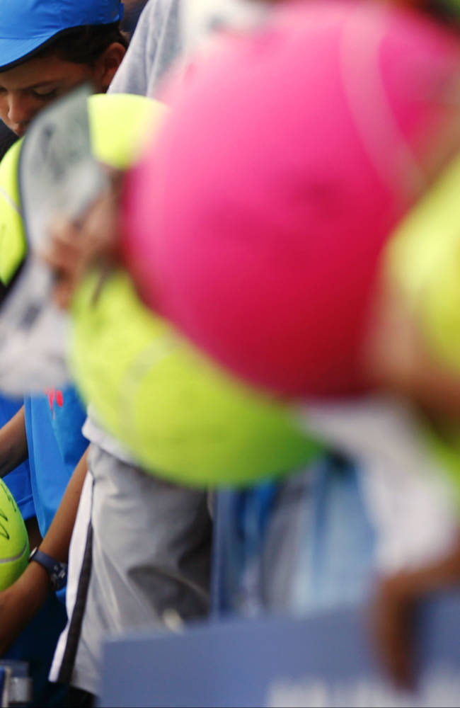 A young fan waits at court side for an autograph from Jo-Wilifried Tsonga, of France, during the second round of the 2014 U.S. Open tennis tournament, Thursday, Aug. 28, 2014, in New York