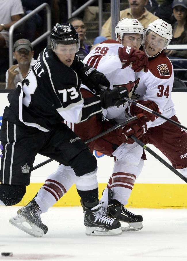 Phoenix Coyotes Michael Stone (26) and Tim Kennedy (34) collied as Los Angeles Kings  Tyler Toffoli (73) controls the puck during the second period of an NHL hockey game at the Staples Center Sunday, April 15, 2013., in Los Angeles