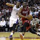 Miami Heat's Dwyane Wade (3) drives to the basket as Sacramento Kings' Rudy Gay (8) defends in the first half of an NBA basketball game, Friday, Dec. 20, 2013, in Miami. (AP Photo/Lynne Sladky)