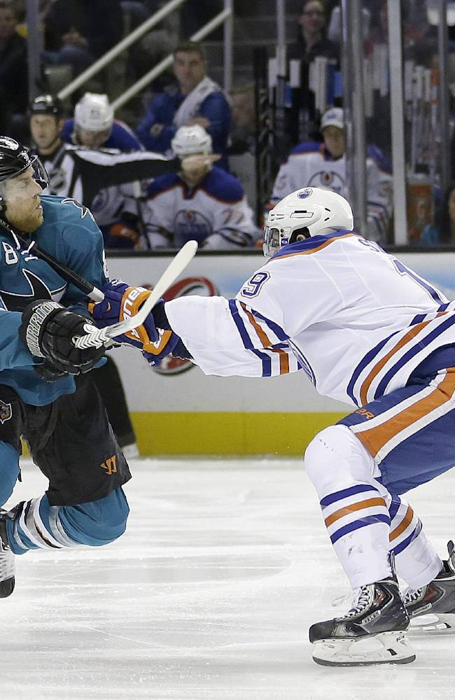 San Jose Sharks center Joe Pavelski (8) tries to get around Edmonton Oilers defenseman Justin Schultz (19) during the first period of an NHL hockey game Tuesday, April 1, 2014, in San Jose, Calif
