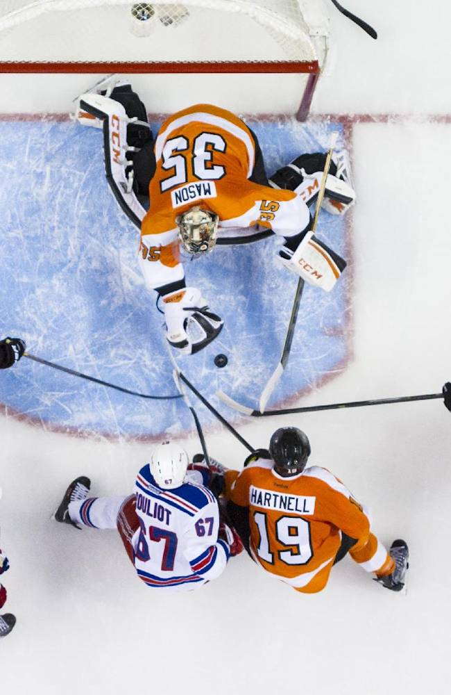 Philadelphia Flyers' Steve Mason, top, reaches for the puck as Luke Schenn (22) Scott Hartnell (19) and Jakub Voracek (93), of the Czech Republic, look to help with New York Rangers' Benoit Pouliot, center left, and Marc Staal, bottom left, looking for a rebound during the third period in Game 4 of an NHL hockey first-round playoff series on Friday, April 25, 2014, in Philadelphia. The Flyers won 2-1