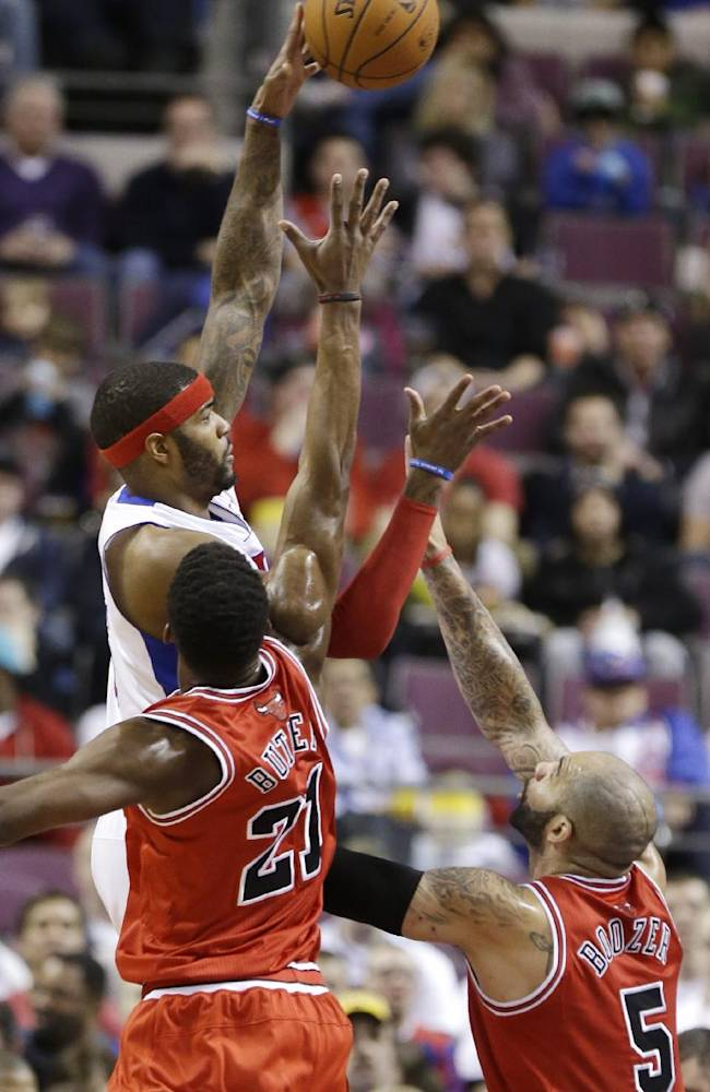 Detroit Pistons forward Josh Smith (6) shoots over the defense of Chicago Bulls guard Jimmy Butler (21) and forward Carlos Boozer (5) during the first half of an NBA basketball game in Auburn Hills, Mich., Wednesday, March 5, 2014