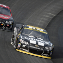 Jimmie Johnson, front, races in front of Mike Bliss during the NASCAR Sprint Cup series auto race, Sunday, Sept. 28, 2014, at Dover International Speedway in Dover, Del. Johnson finished the race in third place. (AP Photo/Nick Wass)