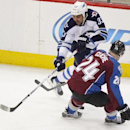 Winnipeg Jets' Dustin Byfuglien (33) passes the puck behind Colorado Avalanche's Marc-Andre Cliche (24) during the third period of an NHL hockey game on Monday, March 10, 2014 in Denver. The Avalanche won 3-2 The Associated Press